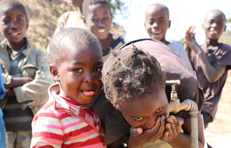 Two-children-take-a-refreshing-drink-of-water-from-a-tap-in-Chingola's-Hellen-settlement